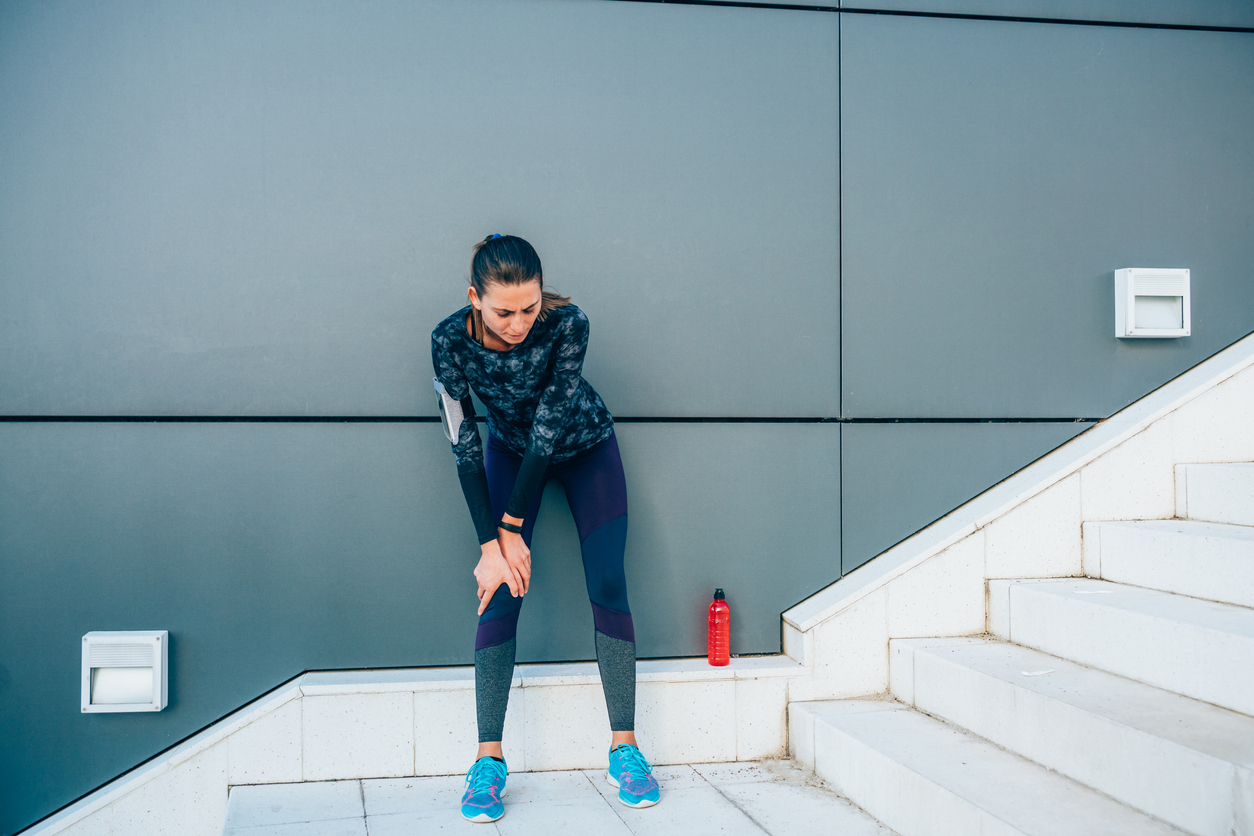 woman having knee pain going up stairs
