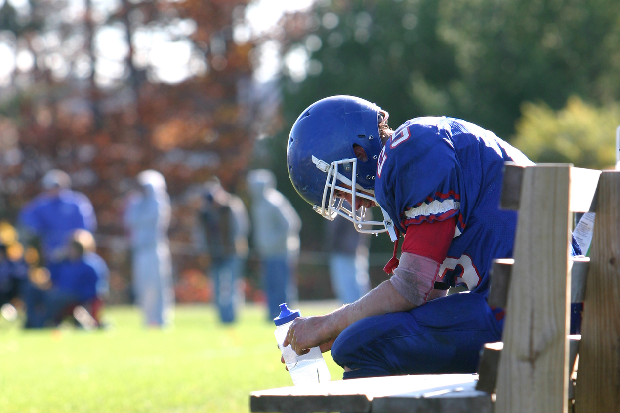 student athlete sitting on bench during football game