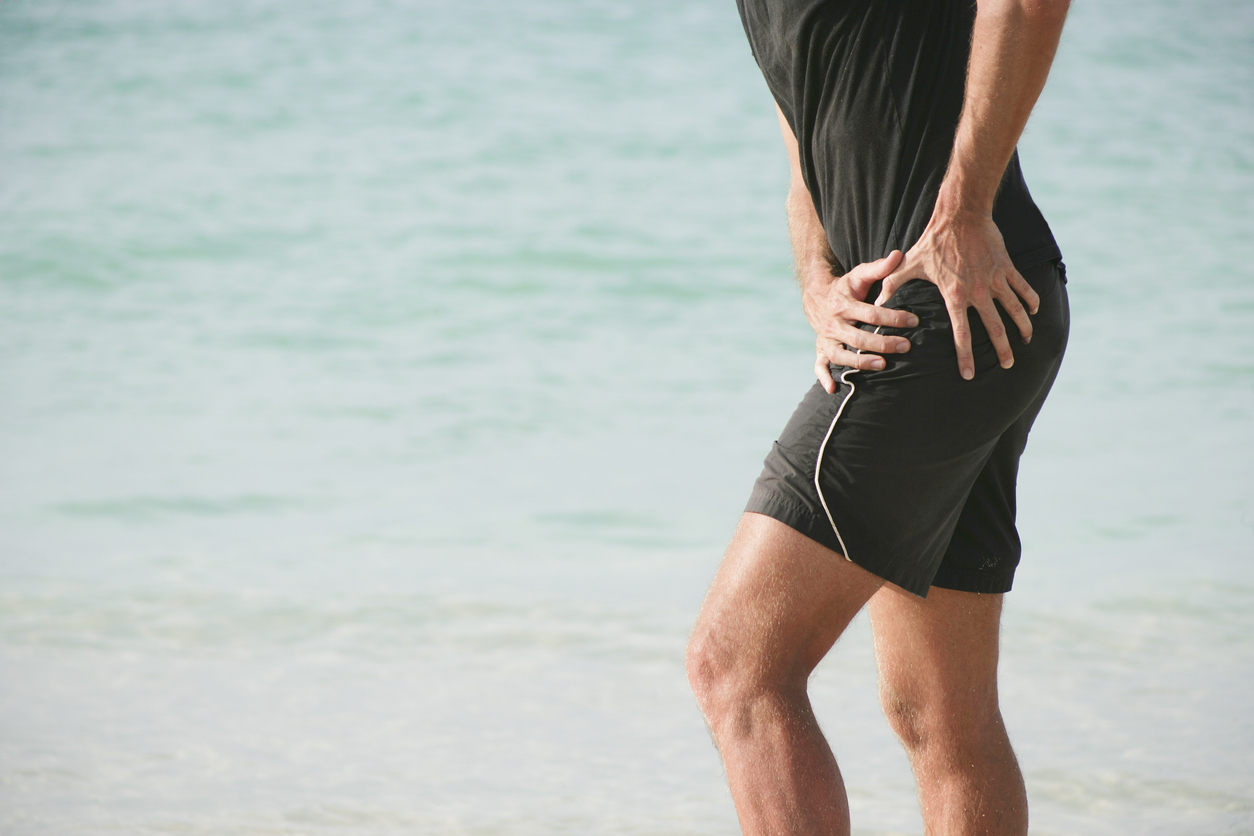 man experiencing hip pain on the beach